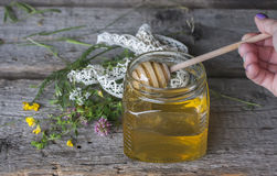Fresh natural honey in a jar with honey spoon on vintage wooden Royalty Free Stock Photo