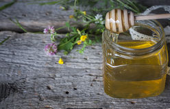 Fresh natural honey in a jar with honey spoon on vintage wooden Royalty Free Stock Photos