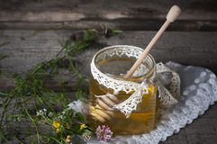 Fresh natural honey in a jar with honey spoon on vintage wooden Stock Photography