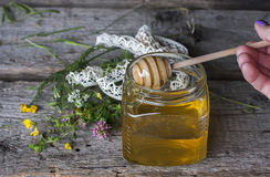 Fresh natural honey in a jar with honey spoon on vintage wooden Royalty Free Stock Images
