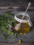 Fresh natural honey in a jar with honey spoon on vintage wooden Stock Photo