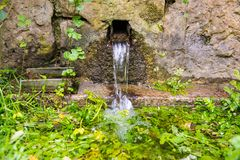 Fresh natural spring fountain. A fresh natural old fountain with mineral water coming out of the spring. Faucet with fresh spring water flowing in the outdoors royalty free stock images