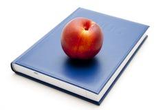 Fresh nectarine on blue book Stock Photo
