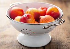 Fresh nectarines and plums in colander Stock Images
