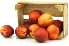 Fresh nectarines in a wooden crate Stock Photos