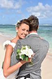 Fresh newly-weds on the beach holding eachother Royalty Free Stock Images