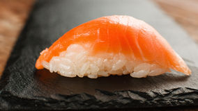Fresh nigiri salmon sushi on black slate, close up. Appetizing and fresh one nigiri salmon sushi served on black slate, close up. Japanese seafood, healthy food Stock Photos