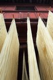 Fresh noodle drying on drying rack. In front of traditional asian house royalty free stock photos