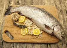 Fresh Norwegian rainbow trout with lemon and onions on a wooden background.  Stock Photography