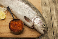 Fresh Norwegian rainbow trout with lemon red caviar, and onions on a wooden background Stock Photo
