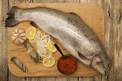 Fresh Norwegian rainbow trout with lemon red caviar, and onions on a wooden background.  Royalty Free Stock Photos