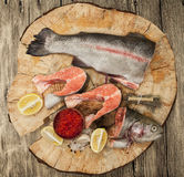 Fresh Norwegian rainbow trout with lemon red caviar, and onions on a wooden background.  Royalty Free Stock Image