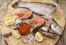 Fresh Norwegian rainbow trout with lemon red caviar, and onions on a wooden background.  Stock Photos