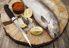 Fresh Norwegian rainbow trout with lemon red caviar, sea salt, knife and onions on a wooden background.  Stock Photos