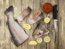 Fresh Norwegian rainbow trout with lemon red caviar, sea salt, knife and onions on a wooden background Stock Photos