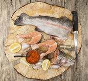 Fresh Norwegian rainbow trout with lemon red caviar, sea salt, knife and onions on a wooden background Royalty Free Stock Photo
