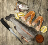 Fresh Norwegian rainbow trout with lemon red caviar. Sea salt, knife and onions on a wooden background Stock Photo