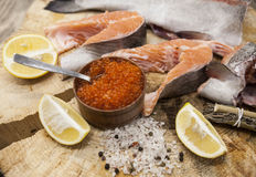 Fresh Norwegian rainbow trout with lemon red caviar, sea salt and onions on a wooden background.  Stock Photo