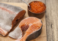 Fresh Norwegian rainbow trout with red caviar on a wooden background.  Royalty Free Stock Photography