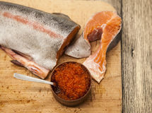 Fresh Norwegian rainbow trout with red caviar on a wooden background.  Royalty Free Stock Photos