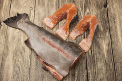 Fresh Norwegian rainbow trout steaks lying on the wooden background.  Stock Image