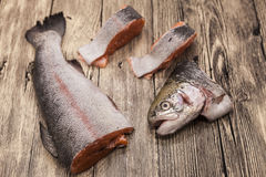 Fresh Norwegian rainbow trout steaks lying on the wooden background Royalty Free Stock Photo