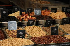 Fresh nuts on a market stall. Text on tags: names and prices of various nuts in Dutch, white and brown hazel nuts, pistacho, para and cashew royalty free stock image