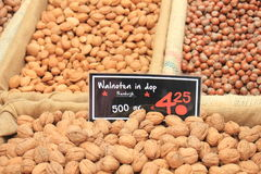 Fresh nuts on a market stall. Fresh unpealed nuts on a market stall text on tags: names and prices of various nuts in Dutch, walnuts, Pecan, almonds and hazel stock image