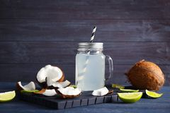 Fresh nuts and mason jar with coconut water. On wooden background Stock Image