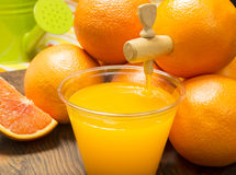Fresh o j pouring from fruit into glass. Fresh orange juice pouring from a spout in a orange and filling a glass on breakfast counter top royalty free stock images