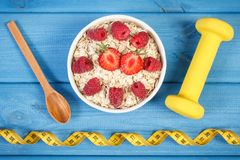 Fresh oatmeal with strawberries and raspberries, centimeter and dumbbells, healthy lifestyle and nutrition. Fresh prepared oatmeal with strawberries and Stock Photos