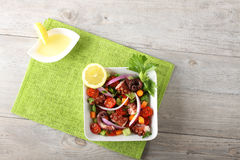 Fresh octopus salad with tomato and onion. On complex background Royalty Free Stock Images