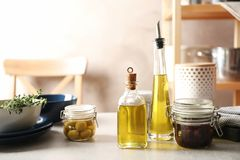 Fresh olive oil and kitchen utensils. On table stock photo
