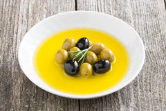 Fresh olive oil and olives in a plate Stock Images