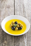 Fresh olive oil and olives in a plate, vertical Stock Images