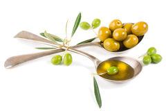 Fresh olive oil and olives in a two spoons Royalty Free Stock Images