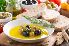 Fresh olive oil in plate and Italian snacks Royalty Free Stock Photos
