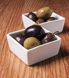 Fresh olives. In a white bowl, on wooden background Royalty Free Stock Photos