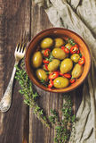 Fresh olives with chili pepper and thyme in bowl. On rustic wooden background Stock Image
