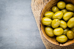 Fresh olives and gray background. Olives in bowl and spoon. Royalty Free Stock Photos