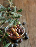 Fresh olives and olive branch on wood background Stock Photo