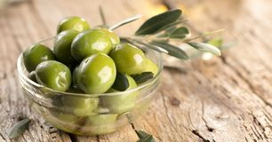 Fresh olives and olive oil on rustic wooden background. stock image