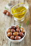 Fresh olives in white bowl on wooden table Royalty Free Stock Photo