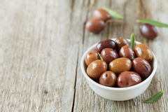 Fresh olives in white bowl on wooden table Royalty Free Stock Images