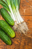 Fresh onion and cucumbers on old rustic wooden table. At a countryside farm Royalty Free Stock Image