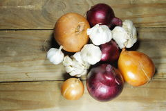 Fresh onion and garlic on wooden table Stock Image