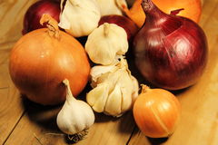 Fresh onion and garlic on wooden table Royalty Free Stock Image