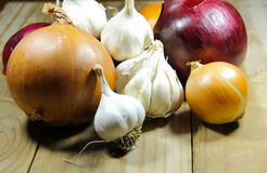 Fresh onion and garlic on wooden table Royalty Free Stock Photos