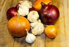 Fresh onion and garlic on wooden table Stock Images