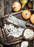 Fresh onion with old hatchet on a cutting board. On a wooden background Stock Photos